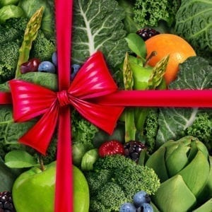 Healthy food gift concept as a group of fresh fruit and vegetables with a red silk bow packaging ribbon as a diet and fitness lifestyle metaphor and symbol for nutritious holiday giving.